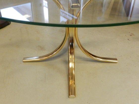 Runt soffbord med klar glasskiva samt benställning i mässing. 104 cm i diameter samt 50 cm hög