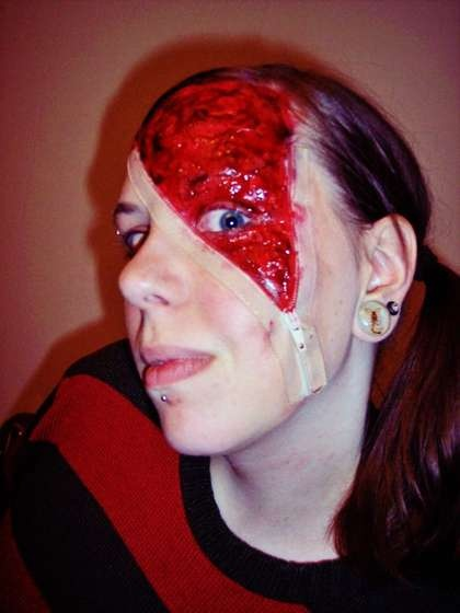 Another take on the zipper-face costume.  I like this idea, but without the blood and gore (I don't want to scare the library patrons or my kids).  Maybe unzipping to a lizard-like face beneath?
