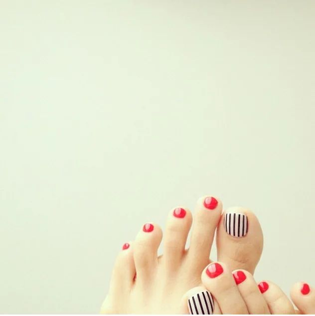 Read toe polish with black and white stripe accent nail