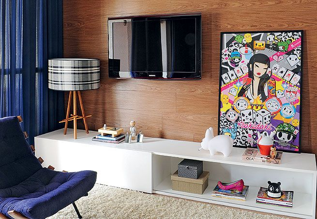 O estilo neutro foi adotado na sala de estar do casal, que ganhou revestimento de madeira na parede para dar profundidade à sala. O colorido ficou por conta dos objetos de design, da cadeira Costela e das cortinas azul-marinho  Marcelo Magnani / Casa e Jardim
