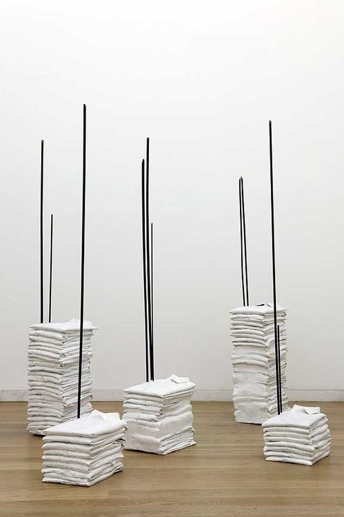 This untitled installation, made in 1990, was in direct response to an incident in Colombia in 1988, where male banana plantation workers were dragged from their homes and murdered. The shirts are bright white, carefully laundered and folded, piled up and waiting to be worn. Steel poles pierce each pile, pinning them to the floor. This piercing of the soft white cotton, with hard steel, implies a violent interruption. Doris Salcedo.