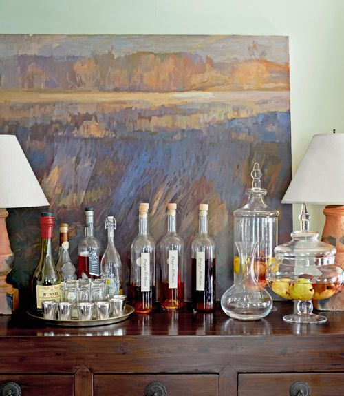 Windley's oil painting of the 20-acre property sits atop an elm sideboard her husband bought in Shanghai for $400. DiMauro made the beautifully bottled infused grappas (center).   - CountryLiving.com