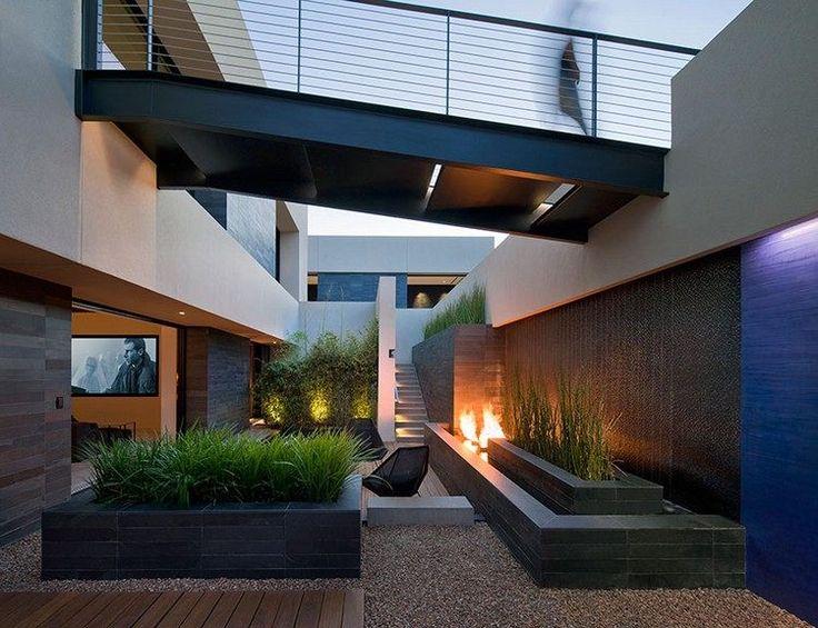 cour intérieure moderne aménagée avec une cheminée contemporaine, des parterres surélevés avec graminées d'ornement et gravier décoratif