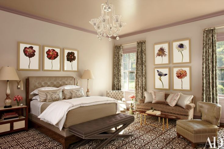 Photographs of wilting flowers by Rachel Lévy animate the master suite; the Barovier & Toso chandelier is vintage, and Gambrel designed the upholstered bed. The bench, tufted chair, and sofa are covered in fabrics by Schumacher, Armani/Casa from Donghia, and Pierre Frey, respectively; the curtain material is by Donghia, and the rug is by Beauvais Carpets.
