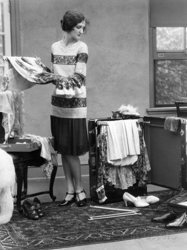 Woman packing clothes for travel , 1920s