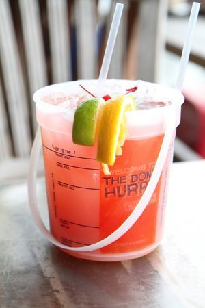 Recipe for Voodoo Punch Bucket: Start with a large glass (preferably a fun container that can hold more than 20 ounces of fluid). Add ice to container. Add 1.5 each of pineapple, mango, coconut and banana rum. Fill with equal parts cranberry and orange juice. Garnish with lime, orange and two cherries.