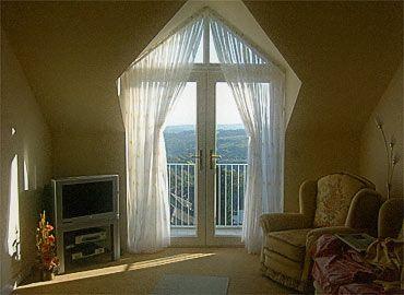 Full length windows with floaty curtain leading to balcony