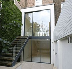 A double height rear extension with slim framed sliding glass doors to both floors and integrated frameless balustrading