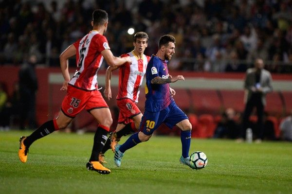 Girona's defender Juanpe Ramirez (L) vies with Barcelona's forward from Argentina Lionel Messi during the Spanish league football match Girona FC vs FC Barcelona at the Montilivi stadium in Girona on September 23, 2017. / AFP PHOTO / Josep LAGO