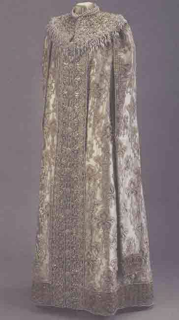 Grand Duchess Xenia Alexandrovna dress worn to the Imperial Russian Ball of 1903. Of white silk, woven with white velvet and gold thread; it is lined with more white silk and trimmed with gold braid and artificial pearls in the lap and sleeves.  On display at The a Hermitage Museum in Saint Petersburg.