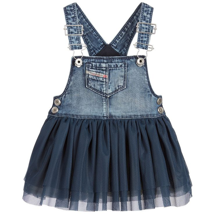Baby girls blue pinafore dress by Diesel. The bib and straps are in soft cotton denim, with a deliberately faded and worn look. The adjustable shoulder straps, fasten with metallic clips on the front and there are poppers on the sides to help with dressing. The skirt is made in soft layers of a blue mesh-effect fabric, with a soft cotton lining.