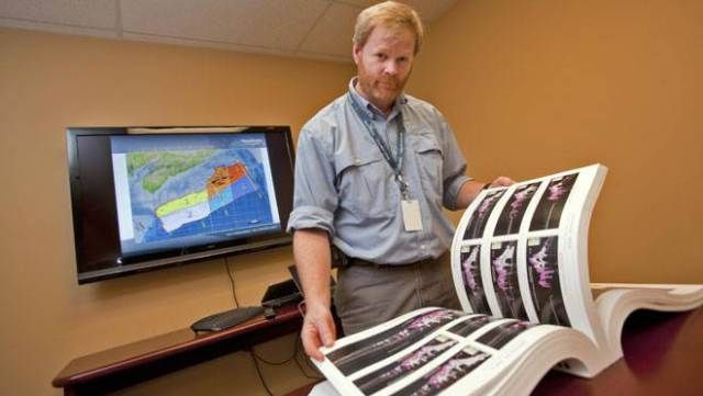 How one man's wild geological treasure hunt could set off a new great oil boom - Sandy MacMullin with Nova Scotia's offshore exploration atlas, the result of his quest.