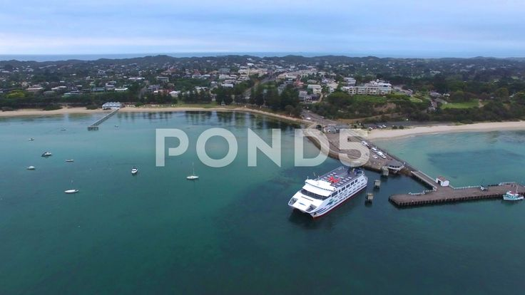 Slow rise above moored ferry at Sorrento revealing the coastline and su - Stock Footage | by gregbrave