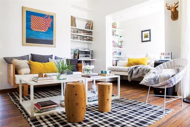Una casa con base neutra y detalles de color  Sobre el sofá diseñado por el estudio Galliano-Rivolta, almohadones rayados y amarillos de terciopelo (todos de Good Luck Casa). En el centro, alfombra (Dash
