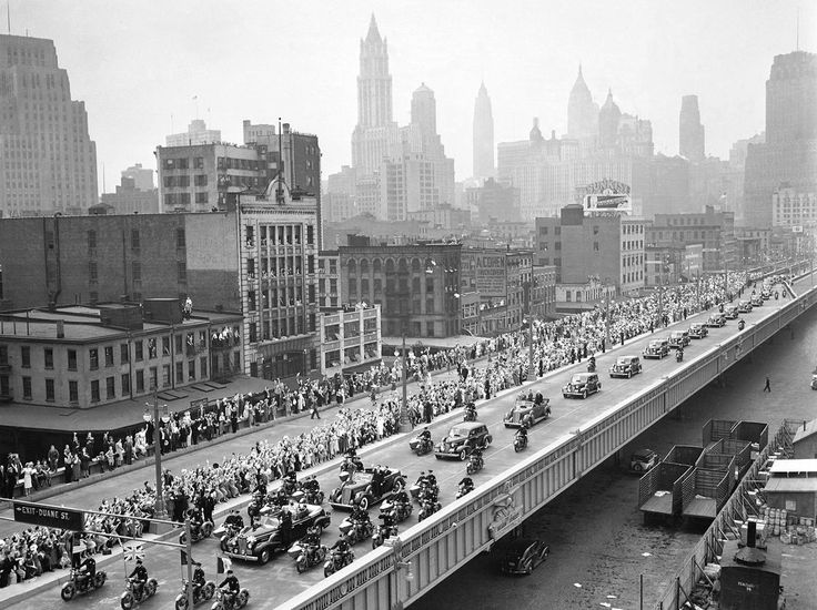 With New York City as a backdrop, King George VI and Queen Elizabeth (first car) proceed up the Westside highway along the Hudson en route to the New York World's Fair, on June 10, 1939, soon after they landed at the Battery. A score of New York motorcycle police surrounded the royal car, and several men stood guard on the running boards.