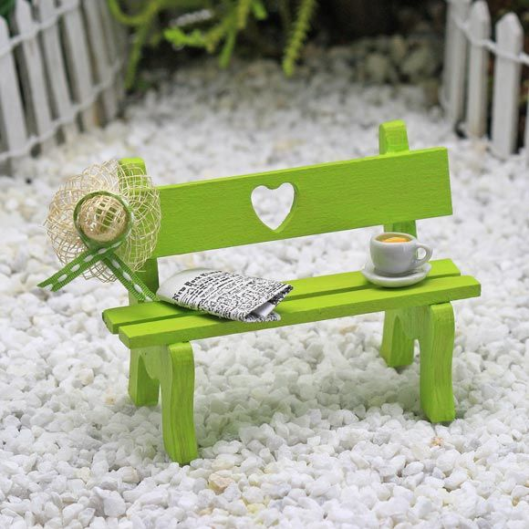 Green fairy garden bench with straw hat, newspaper cup of tea and heart motif