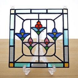 4つの花が並んだ可愛らしい図案のステンドグラス ミニパネルです。明るい色合いで、リビングやキッチン、ベッドルームなどどんな場所にもなじみます。パネル上部には吊り下げ用の金具が付いていますので、お手持ちのチェーンや紐で吊り下げて飾ることができます。陽のあたる窓際に吊り下げると、ガラスの色が鮮やかに(濃く)浮き上がり、とてもきれいです。お好みで飾る向きを変えていただけます。作品は自立しませんが、壁に立てかけたりお手持ちの皿立てに立てかけて飾ることも可能です。その場合は倒れて割れないよう布などを敷くことをお勧めします。 リビングボードの上や、飾り小窓、出窓などに飾っても素敵です。DIYが得意な方は、ドアや壁にはめこんたり額に入れて飾ってみてはいかがでしょうか。大きさ:たて約15cm×よこ約15cm×厚さ約3mm 重さ:約190g 素材:ガラス、鉛●ご購入の前に必ずご確認ください。作品はすべてハンドメイドの一点ものです。 ガラス作品のため、光のあたり具合によって色の見え方や透明感が違ってきます。…