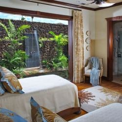 Stunning bedroom in Hawaii island-inspired retreat features an outdoor garden shower.