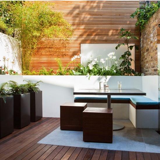 Aqui construi-se um muro branco proximo ao muro do fundo, criando uma floreira mais alta e encosto para o banco.Parede revestida em madeira ambienta o jardim.