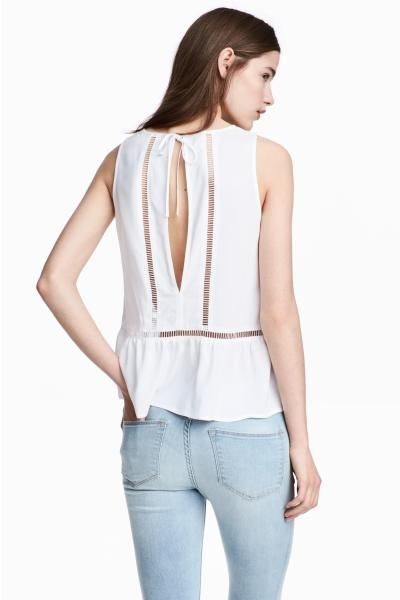 Sleeveless top in a soft viscose weave with inset hemstitch embroidery. Opening at the back with ties at the back of the neck and a flounced hem.