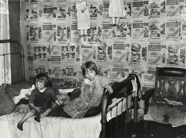 """Description on back of picture: """"Two filthy girls, covered in coal dust, sitting on a double bed. The wall behind them is papered with Post Toasties Corn Flakes boxes."""" Charleston, WV 1938 photographer ~ Marion Post Wolcott"""