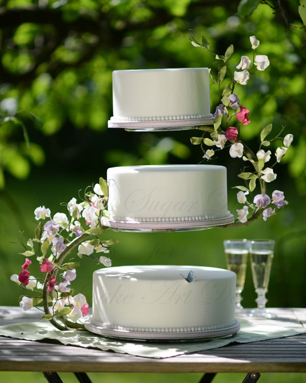 a midsummer night dreams wedding cake with flowerpaste sweet peas wired to a s