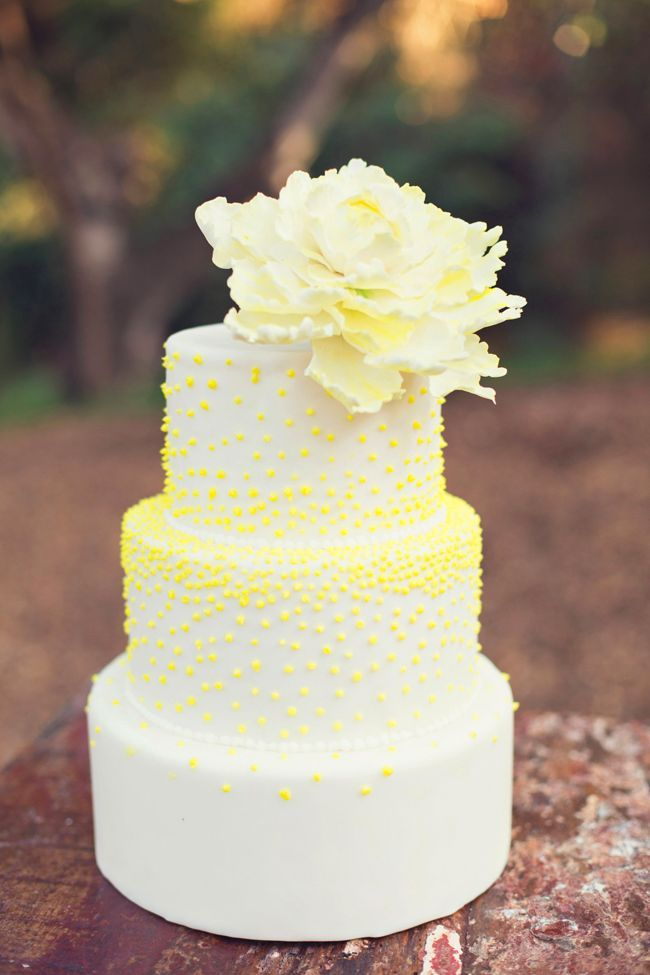 White wedding cake with a smattering of fluorescent Yellow dots and am off centre sugar flower. Wedding Cakes