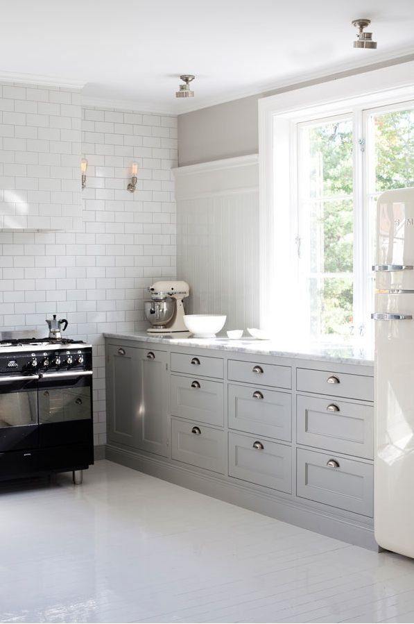 I love the simplicity of this kitchen.  The white painted floors and the grey storage.  Perfect! image via