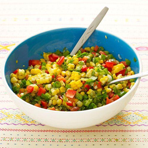 Kook de maïs in gezouten water in 4–5 minuten tot-ie net gaar is.    Laat uitlekken en iets afkoelen. Snijd de lente-uitjes, paprika's, chilipeper, koriander en munt fijn, en doe dit alles in een kom.Haal de maïskorrels van de kolven en voeg...