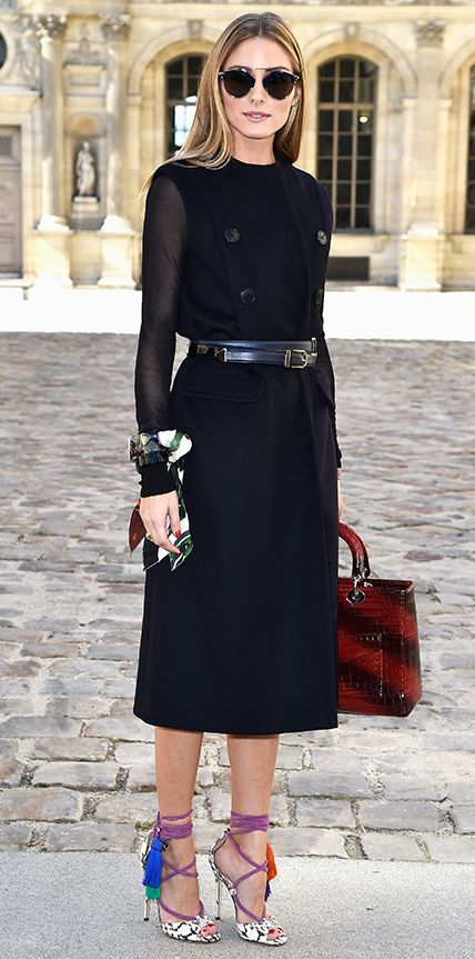 Olivia Palermo sat perched in the front row of the Dior spring/summer 2015 show during Paris Fashion Week in a black double-face wool Dior coat dress (with sheer sleeves) that she belted at the waist, accessorizing with a printed Dior scarf bracelet, Dior sunnies, a red Dior croc handbag, and lace-up tasseled Jimmy Choo heels.