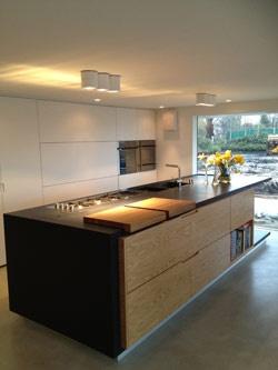 Dit huis heeft binnen een grote keuken, een heel erg groot  bruin aanrecht(blad) met een bloemetje erop in een vaas en veel witte keukenkastjes.
