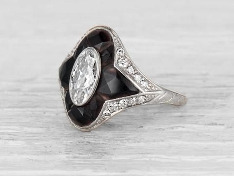 Art Deco Tiffany & Co ring made in platinum centered with an EGL certified approximately .90 carat E-F color VS1 clarity oval cut diamond surrounded by 8 fancy cut onyx. Accented by 20 single cut diamonds. Circa 1920. Onyx and diamond rings are synonymous with the Art Deco period. This is vintage Tiffany at it's finest. Elongates the hand, but may be difficult to wear with a wedding band. Diamond and gold mining has caused devastation in areas such as Africa, wreaking havoc on delicate…