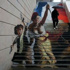 A man passes by an unfinished street art graffiti made in a stairway by French street artists Zag and Sia in Paris