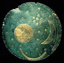 The Nebra sky disk is a bronze disk of around 30 centimeters (12 in) diameter and a weight of 2.2 kilograms (4.9 lb), with a blue-green patina and inlaid with gold symbols. These are interpreted generally as a sun or full moon, a lunar crescent, and stars (including a cluster interpreted as the Pleiades). Two golden arcs along the sides, marking the angle between the solstices, were added later. A final addition was another arc at the bottom surrounded with multiple strokes (of uncertain…