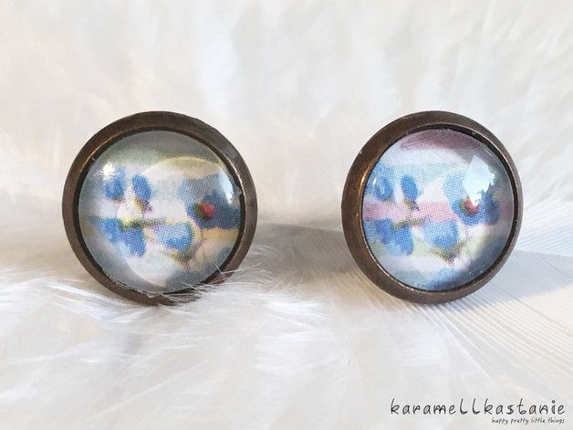 Diese wunderschönen Ohrstecker zeigen zarte blaue Blümchen auf einem in Pastelltönen gestreiften Hintergrund. Perfekt für den Frühling!  Durchmesser Cabochon inkl. Fassung: ca. 1,2 cm  Fassung:...