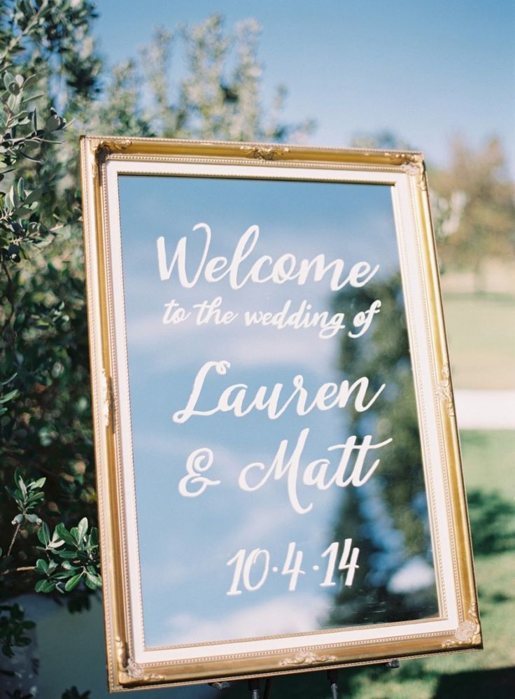 Use a mirror and paint to welcome guests to your wedding.  Photo: Rylee Hitchner | http://emmalinebride.com/decor/wedding-mirror-signs/