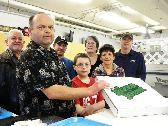 Star Staff  Marc Leduc (left), Brian Johnston, Matt Fex, Aries Johnston, Gabrielle Dominic, Bill Hickey and Rose Wasyluk serve pizza at the Blue Door Soup Kitchen on New Year's Eve Day.