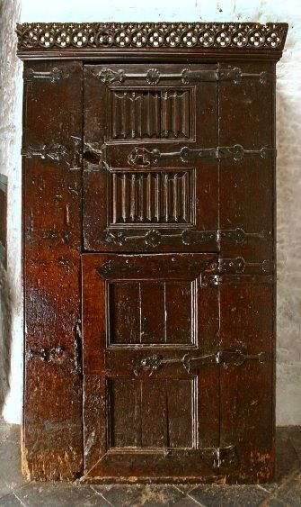 Bunratty Castle Medieval Collection: 15th century French style Oak Press cupboard, the upper door with linenfold decoration, the lower having plain panels. The strap hinges display Gothic type decoration.