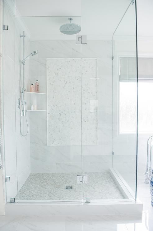 Beautifully designed master bathroom features a seamless glass walk-in shower fitted an exposed plumbing nickel shower kit mounted to marble surround tiles beside stacked corner shelves.