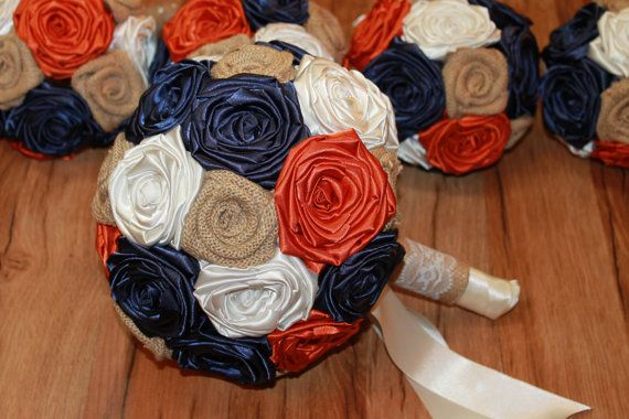 Navy, Pumpkin, Ivory, & Burlap Bouquet Set  Easily add a little cottage chic elegance to your wedding ceremony with this burlap wedding bouquet set from Hey Bouquet. Its the little details that matter most and this delightful set of burlap wedding bouquets will give your wedding party a stunning look that doesnt cost a fortune. Each element is made from hand rolled satin flowers and rustic burlap flowers in a remarkable display of design. The handles of all the bouquets are adorned with l...