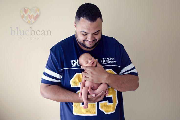 Newborn boy with daddy in a football top.  Blue Bean Photography ~ Newborns www.bluebeanphotography.co.uk www.newbornphotographycoventry.co.uk