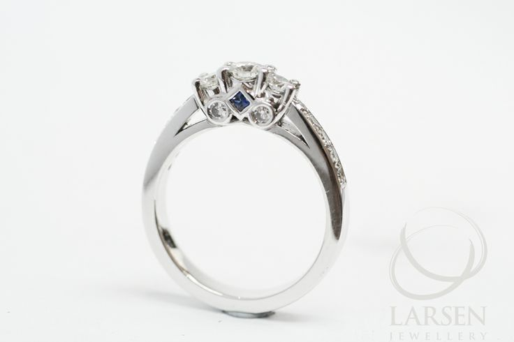 Just a touch of blue! A custom made diamond engagement ring featuring one small Sapphire set into the profile of the setting.  www.larsenjewellery.com.au