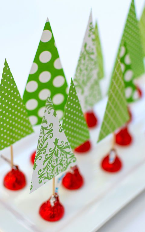 Bring the fun for the kids with this super simple and festive way to create a Christmas table centerpiece. All you'll need is scrapbook paper, toothpicks, tape, and red foil-wrapped Hershey's Kisses.