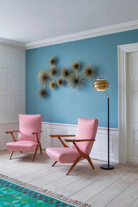 colorful room with pink mcm chairs and a blue wall
