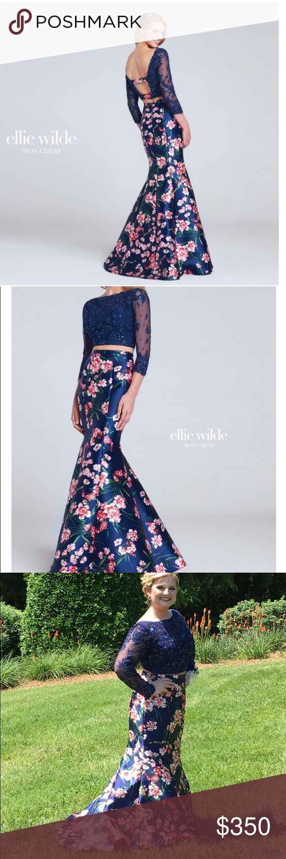 """GORGEOUS Navy & Floral Two-Piece Prom Dress Two-piece long sleeve lace and printed Mikado trumpet dress with bateau neckline that continues over the shoulders into a tapered back with printed Mikado straps. Top is covered in lace with heat set stones, an illusion neckline, sleeves, and back panels. Printed Mikado high-waisted skirt is fitted though hips and thighs then flares into a full skirt and sweep train. Hemmed to fit 5'4"""" with flats. Top was taken in on shoulders and bottom strap…"""
