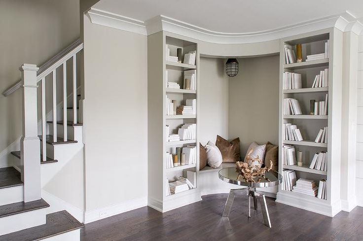 A round chrome coffee table sits in front of a built in corner bench fitted with a gray seat topped with brown and velvet pillows placed against light gray walls lit by a cage pendant light as the bench is flanked by gray built bookcases.