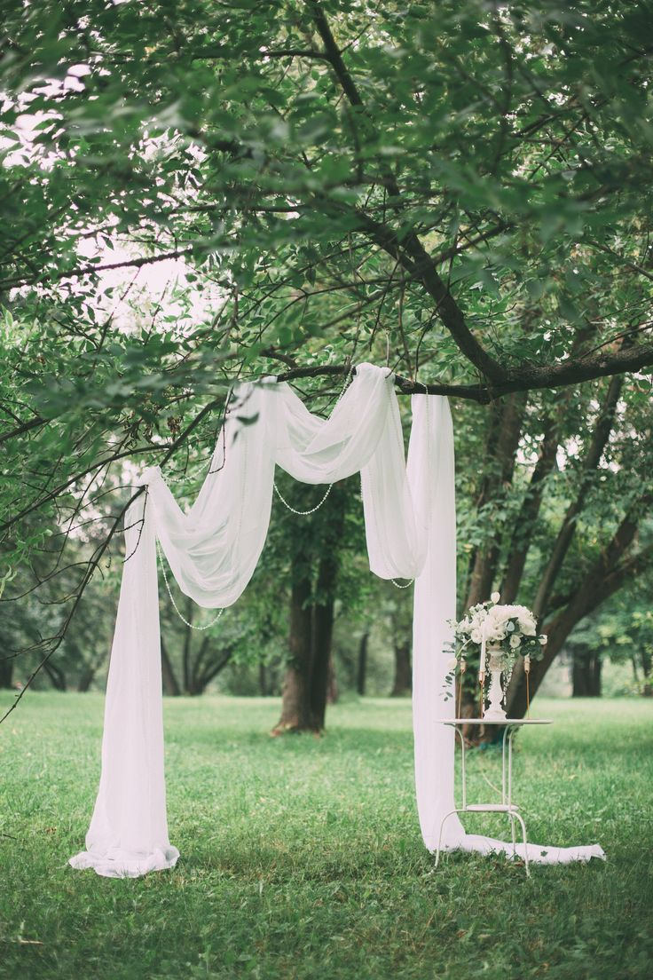 Wedding ceremony in nature, decorated with a white light cloth and a composition with garlands