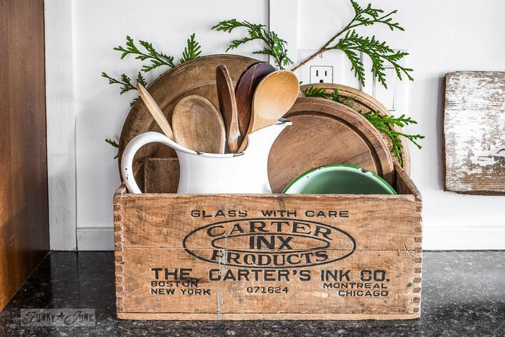 Collection of rustic cutting boards and wooden spoons in a vintage crate and white milk pitcher in a kitchen, part of Funky Junk Interiors' Christmas home tour. See it all at funkyjunkinteriors.net #christmas
