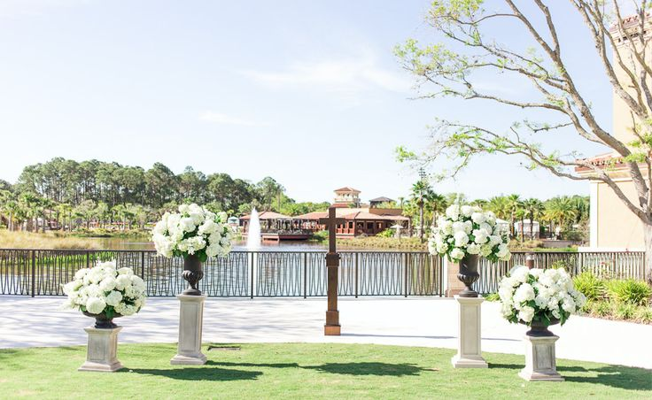 outdoor wedding ceremony featured large and lush traditional urns overflowing with white hydrangea and white stock on pedestals.