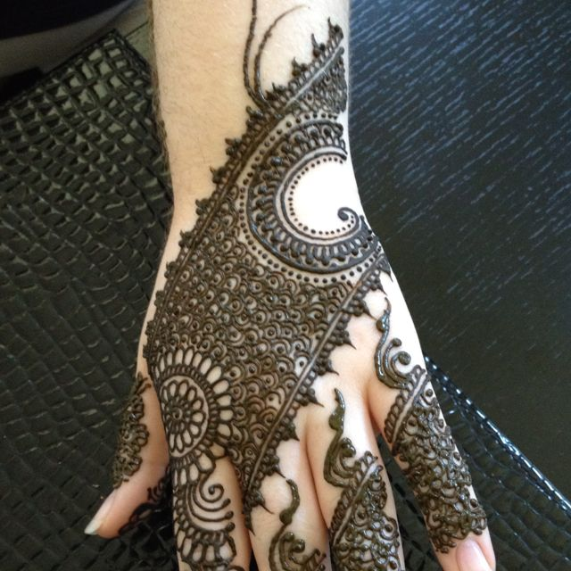 Beautiful intricate wedding mehndi design henna application on Indian bride's hand for a hindu wedding.